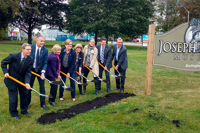Groundbreaking event at Joseph Brant Museum with the Burlington MP, MPP, Mayor, Councillors, Museum Director and Museum Boards holding spades.